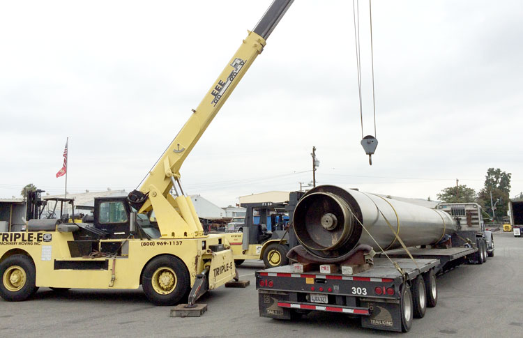 Crane preparing to lift mandrel roll off of trailer.